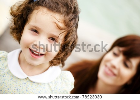 Little child portrait, with her smiling mother in a second term - stock photo