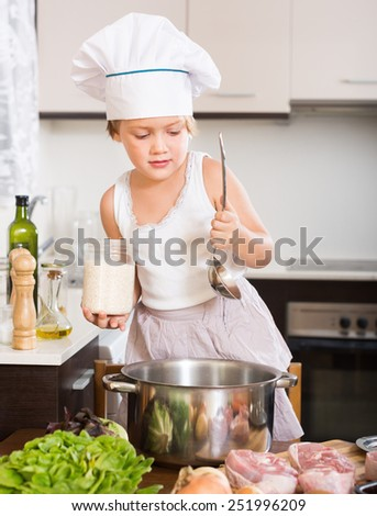 Little child prepared soup at kitchen