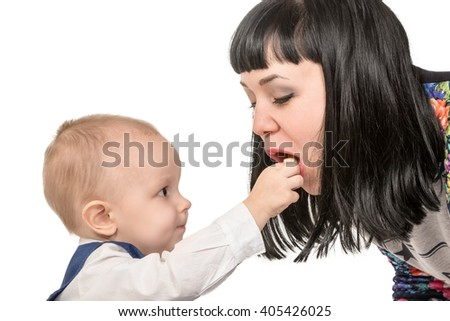 Little child puts in the open mouth of his mother food isolated on white background - stock photo