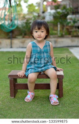 little child sits on a wooden chair in front house yard