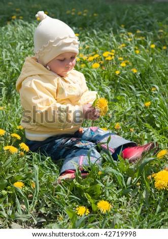 little child sitting among dandelions - stock photo
