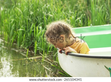 Little child sitting at the boat by a river on summer day. - stock photo