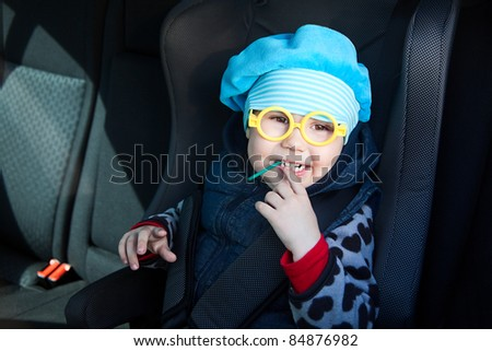 Little child sitting in carseat in vehicle with lollipop. Funny glasses - stock photo