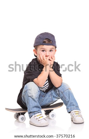 Little child sitting on a skateboard isolated on white background - stock photo