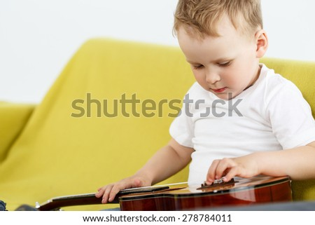 Little child sitting on couch and examine ukulele guitar. Young talented kid holding small four stringed Hawaiian guitar. Musical instrument learning concept - stock photo