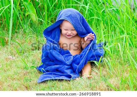 Little child sitting on the grass with blue towel - stock photo