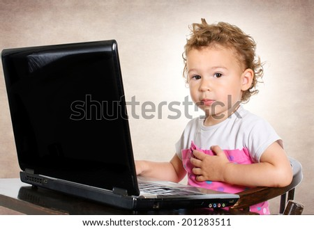 Little child sitting on the laptop computer and looking at camera  - stock photo