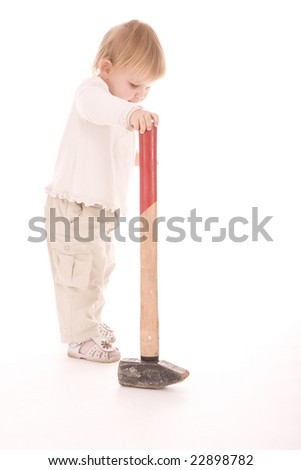 little child standing near big hammer and holding it - stock photo