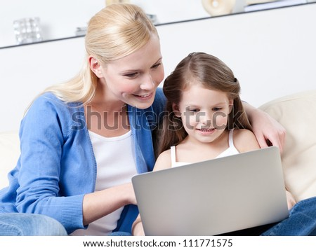 Little child surfs on the internet with her mother sitting on the sofa
