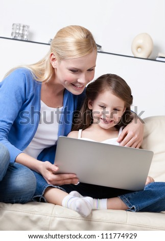Little child surfs on the internet with her mum sitting on white leather sofa