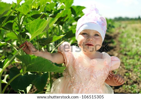 Little child walking in green field