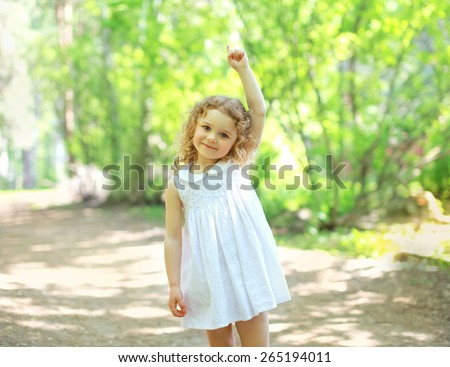 Little child walking in the park and showing up hand, sunny summer day - stock photo