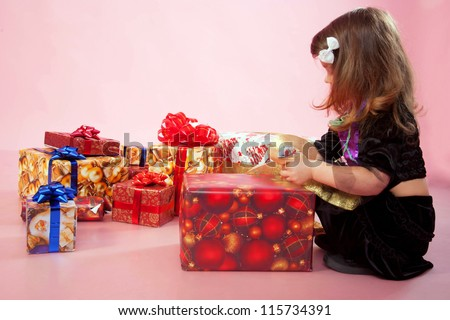 Little child wearing a fairy costume rejoicing and looking at a lot of Christmas gifts or birthday presents on a pink background.
