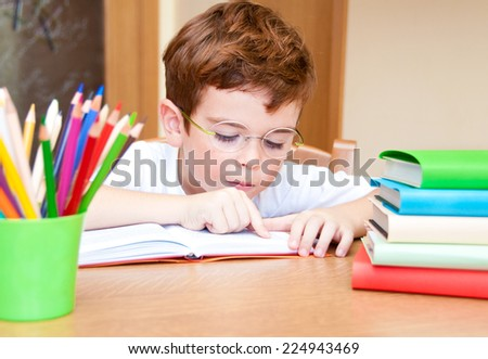Little child wearing glasses reading a book - stock photo