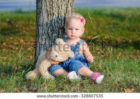 Little child with a teddy bear sits under the tree