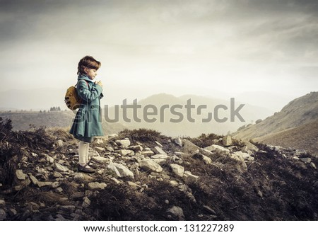 little child with backpack in the mountain - stock photo