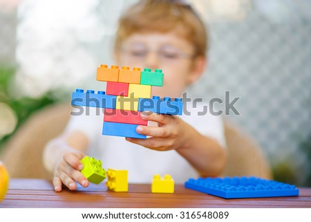 Little child with glasses playing with lots of colorful plastic blocks indoor. kid boy having fun with building and creating. Selective focus on toy