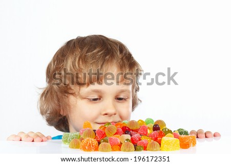 Little child with jelly candies on a white background - stock photo