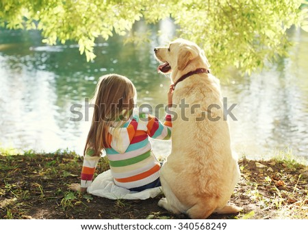 Little child with Labrador retriever dog sitting in sunny summer park near water - stock photo
