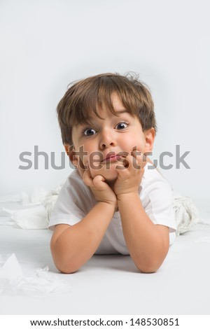 Little child with surprised and funny face has his hands on his chin