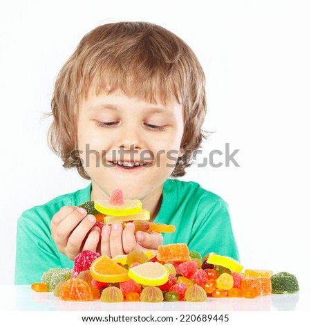 Little child with sweets and jelly candies on a white background - stock photo