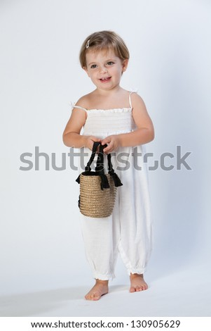 Little child with white dress and little bag. - stock photo