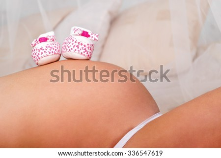 Little children a pair of shoes lying on the pregnant tummy woman closeup - stock photo