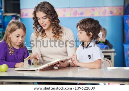 Little children and teacher reading book at desk in preschool - stock photo