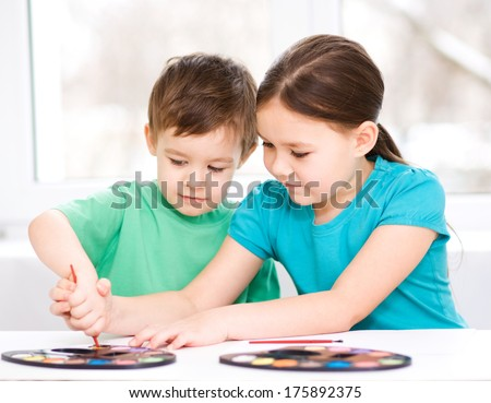 Little children are painting with paint, sitting at table