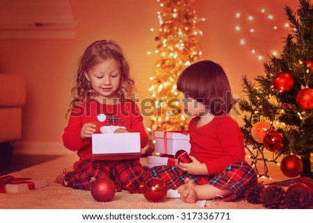 Little children at Christmas Eve. Sister and brother under decorated illuminated Christmas Tree unpacking gifts at home. - stock photo
