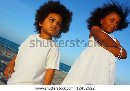Little children at the beach wearing white - stock photo