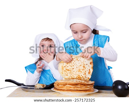 Little children cooking pancakes. Two cute girls playing as chefs. Junior is eating the one. Surprise for Mothers Day. Isolated on a white background. - stock photo