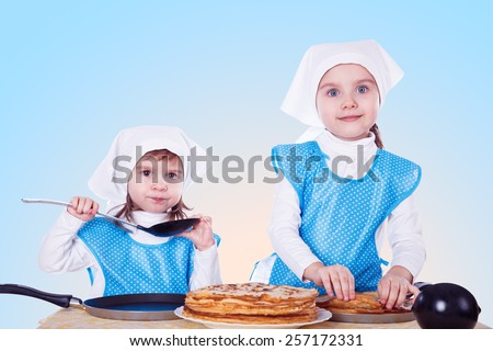 Little children cooking pancakes. Two cute girls playing as chefs. Surprise for Mothers Day.  Blue background. - stock photo