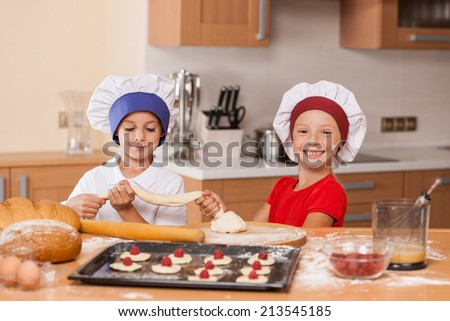 little children holding dough and pulling apart. brother and sister having fun at kitchen table - stock photo