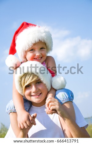 Little children in a santa hat in the summertime