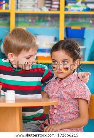 Little children in language camp with flags on cheeks - stock photo
