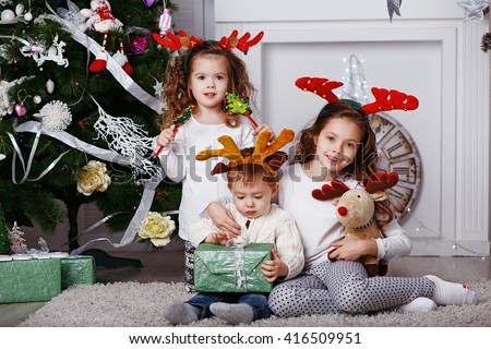 Little children in reindeer antlers In anticipation of new year and Christmas. Three little siblings opening christmas gifts. Kids in comfortable home clothes sitting on floor over Christmas tree - stock photo