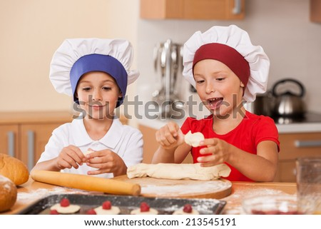 little children making cakes and talking. two little boys having fun at kitchen table  - stock photo