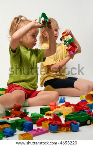 Little children playing with colorful cube blocks - stock photo