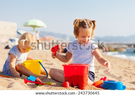 Little children playing with sand at sea