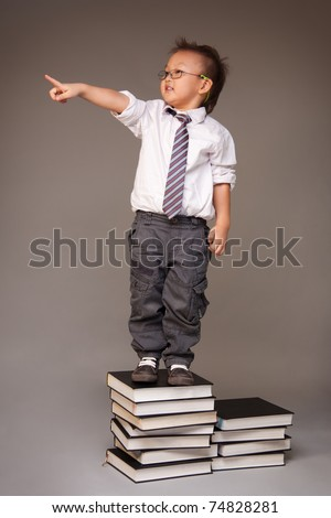 Little Chinese boy entrepreneur standing on stack of books and pointing with his finger - stock photo