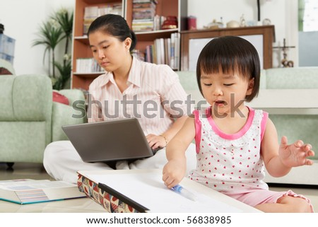 LIttle Chinese girl playing with drawing paper with her mother or nanny on background