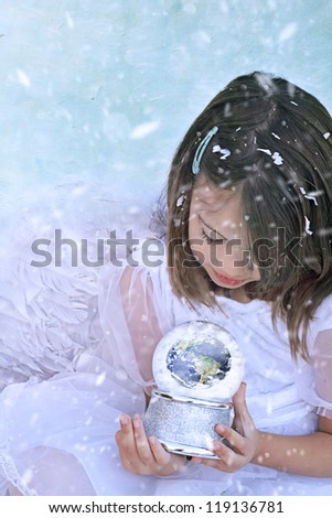 Little Christmas angel in the snow holds a snow globe and watches the earth. Elements of this image furnished by NASA.""
