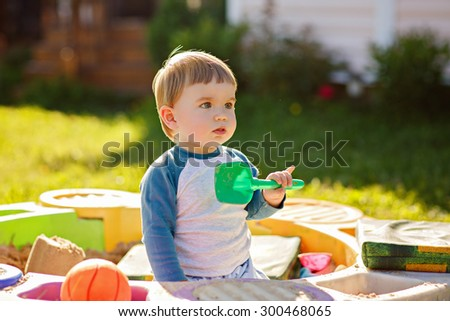 Little chubby toddler boy playing in the sandbox, holding a shovel, summer in Sunny weather