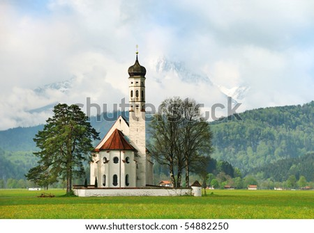 Little church in the countryside with Alps on the background early in the morning