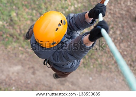 Little climber hanging on a rope - stock photo