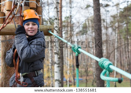 Little climber is ready to the passage the ropes course - stock photo