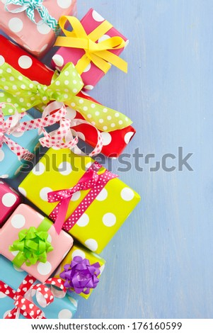 Little colorful gift boxes wrapped in dotted paper - stock photo