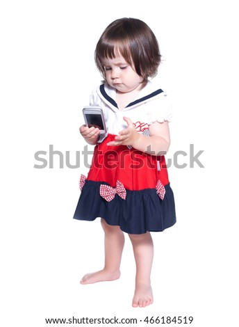Little concentrated girl with a telephone. Isolated on white background.