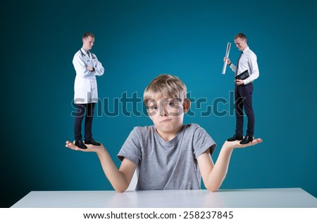 Little confused boy thinking about his future profession - stock photo